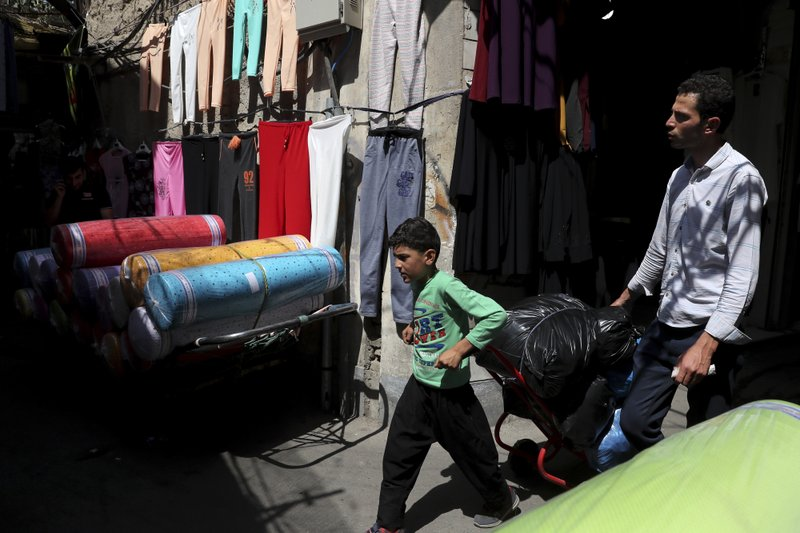 In this June 23, 2019, photo, a young worker pulls his hand cart in the main bazaar in Tehran, Iran. The most-visible place to see the effect of the economic hardship most face comes from walking by any money-exchange shop. Depreciation and inflation makes everything more expensive, from fruits and vegetables to tires and oil all the way to the big-ticket items, like mobile phones. (AP Photo/Ebrahim Noroozi)