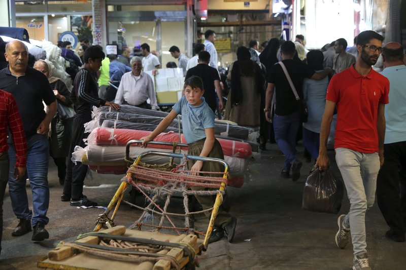 A young worker takes a break on his cart at the old main bazaar in Tehran, Iran, Sunday, June 23, 2019. (AP Photo/Ebrahim Noroozi)