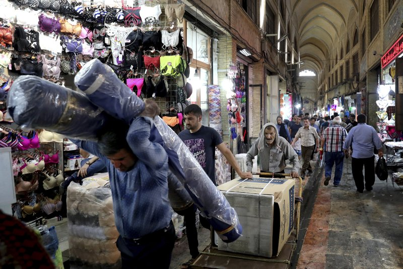 In this June 23, 2019, photo, people carry on about their business in the main bazaar in Tehran, Iran. As the U.S. piles sanction after sanction on Iran, it's the average person who feels it the most. (AP Photo/Ebrahim Noroozi)