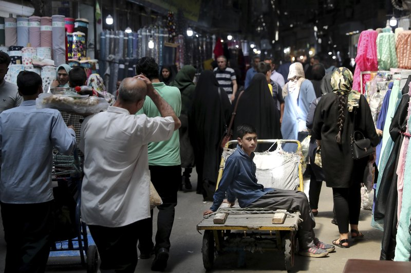 A young worker sits on his hand cart at the old main bazaar in Tehran, Iran, Sunday, June 23, 2019. As the U.S. piles sanction after sanction on Iran, it's the average person who feels it the most. (AP Photo/Ebrahim Noroozi)