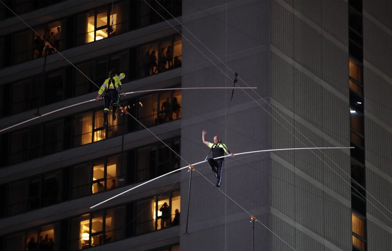 Aerialists Nik Wallenda, right, and his sister Lijana walk on a high wire above Times Square, Sunday, June 23, 2019, in New York. (AP Photo/Jason Szenes)