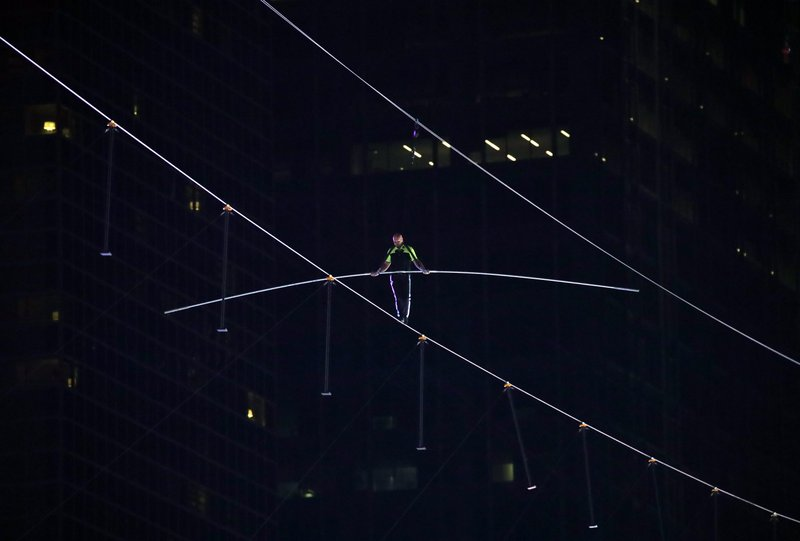Aerialist Nik Wallenda walks on a high wire above Times Square, Sunday, June 23, 2019, in New York. (AP Photo/Jason Szenes)