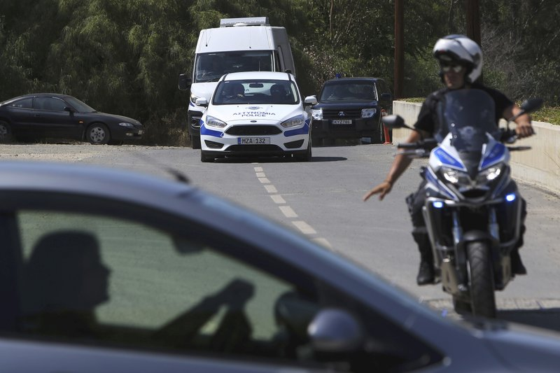 A motorcyclist police officer escorts and guards the police van carrying Army Captain Nicholas Metaxas from the court to the Cypriot central prison in capital Nicosia, Cyprus, Monday, June 24, 2019.  A Cypriot army captain on Monday tearfully apologized to the families of seven foreign women and girls for the
