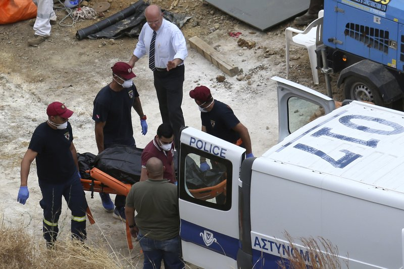 In this photo taken on Tuesday, June 4, 2019, Cyprus' Special Disaster Response Unit investigators carry a covered suitcase on a stretcher after it was retrieved from a man-made lake near the village of Mitsero, outside of the capital Nicosia, Cyprus. A Cyprus criminal court on Monday, June 24, 2019, has sentenced an army captain Nicholas Metaxas, 35, to seven life terms in prison after he pleaded guilty to the premeditated murder and kidnapping of seven foreign women and girls. (AP Photo/Petros Karadjias)