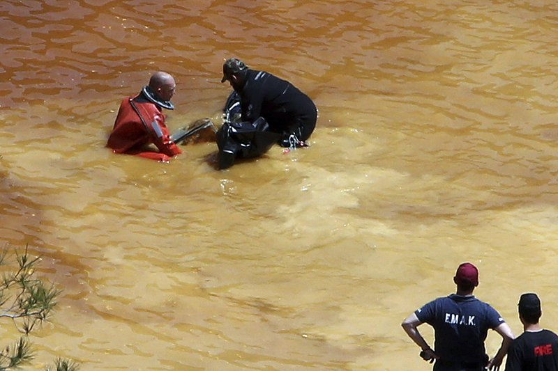 FILE - In this Sunday, April 28, 2019 file photo, a diver, left, and an Investigator remove a suitcase found in a man-made lake, near the village of Mitsero outside of the capital Nicosia, Cyprus. A Cyprus criminal court on Monday, June 24, 2019, has sentenced an army captain Nicholas Metaxas, 35, to seven life terms in prison after he pleaded guilty to the premeditated murder and kidnapping of seven foreign women and girls. (AP Photo/Petros Karadjias, File)