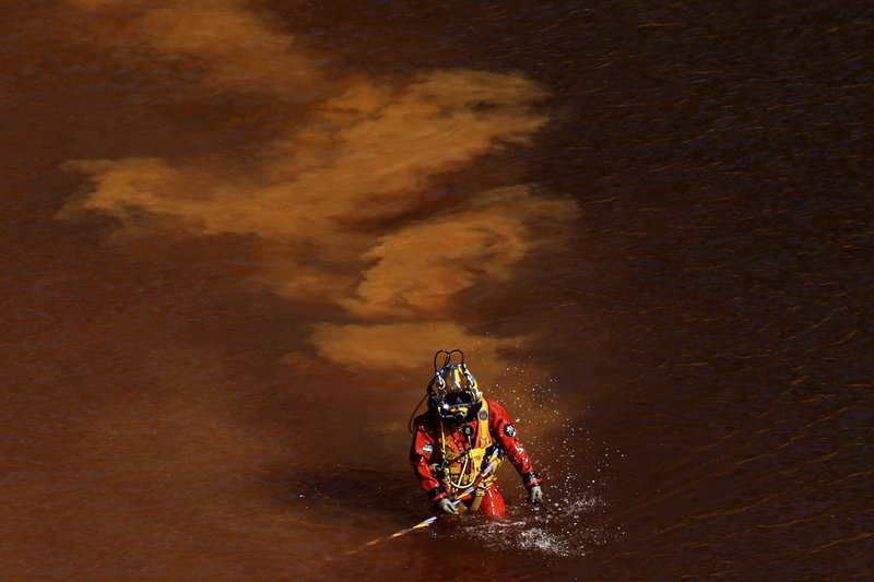 FILE - In this Wednesday, May 8, 2019 file photo, a diver walks out from a toxic man-made lake after a dive search for a third victim near the village of Mitsero outside of the capital Nicosia, Cyprus. A Cyprus criminal court on Monday, June 24, 2019, has sentenced an army captain Nicholas Metaxas, 35, to seven life terms in prison after he pleaded guilty to the premeditated murder and kidnapping of seven foreign women and girls. (AP Photo/Petros Karadjias, File)