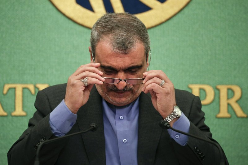 "Iranian Ambassador to Japan Morteza Rahmani Movahed puts on his reading glasses before speaking at a news conference Monday, June 24, 2019, in Tokyo. He said his country faces ""economic terrorism targeting Iranian people"" as U.S. piles sanction after sanction on the country. (AP Photo/Jae C. Hong)"