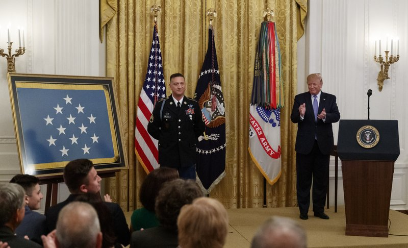 President Donald Trump applauds during a ceremony to award the Medal of Honor to Army Staff Sgt. David Bellavia in the East Room of the White House in Washington, Tuesday, June 25, 2019, for conspicuous gallantry while serving in support of Operation Phantom Fury in Fallujah, Iraq. (AP Photo/Carolyn Kaster)