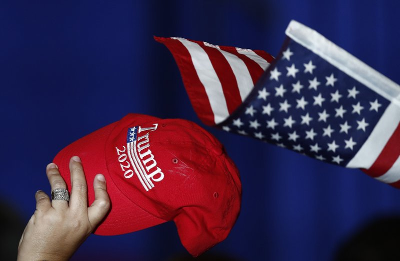 A support holds up a Trump 2020 hat and an American flag as Vice President Mike Pence speaks during a rally on Tuesday, June 25, 2019 in Miami. (AP Photo/Brynn Anderson)