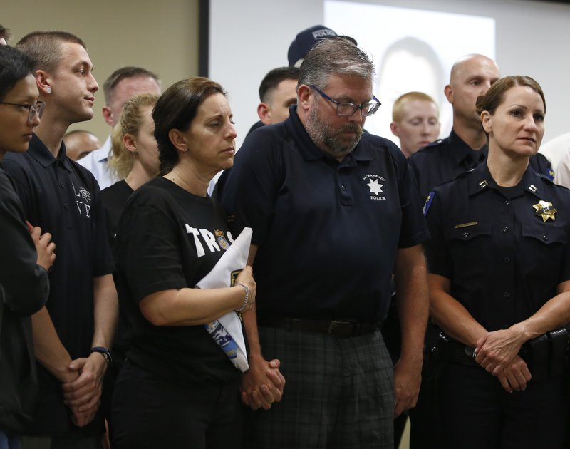 CORRECTS FIRST NAME TO KELLEY, NOT KELLY - Kelley and Denis O'Sullivan, the parents of slain Sacramento Police officer Tara O'Sullivan, hold hands during a news conference in Sacramento, Calif., Tuesday, June 25, 2019. Denis O'Sullivan told reporters that any notion that the Sacramento Police Department was responsible for her death was extremely offensive and hurtful. It took rescuers 45 minutes to reach Tara O'Sullivan after she was shot by gunman, who kept shooting at police, during a domestic violence call last week. (AP Photo/Rich Pedroncelli)