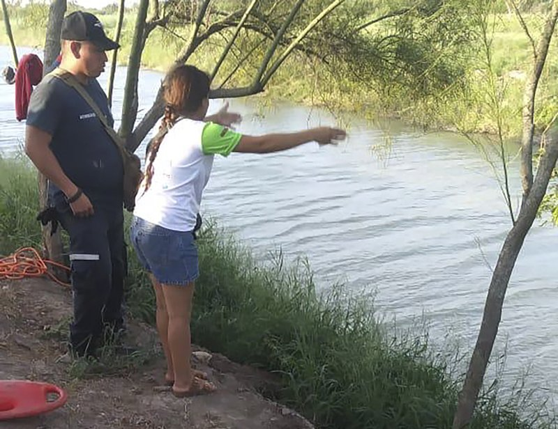 In this Sunday, June 23, 2019 photo, Tania Vanessa Ávalos of El Salvador speaks with Mexican authorities after her husband and nearly two-year-old daughter were swept away by the current in Matamoros, Mexico, while trying to cross the Rio Grande to Brownsville, Texas. Their bodies, the toddler still tucked into her father's shirt with her arm loosely draped around him, were discovered Monday morning several hundred yards from where they had tried to cross. (AP Photo/Julia Le Duc)