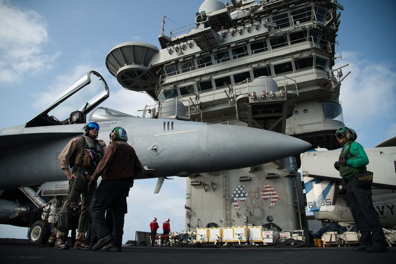 FILE - In this June 3, 2019 file photo, a pilot speaks to a crew member by an F/A-18 fighter jet on the deck of the USS Abraham Lincoln aircraft carrier in the Arabian Sea.  As Iran prepares to break through limits set by its 2015 nuclear deal with world powers, each step narrows the time its leaders would need to have enough highly enriched uranium for an atomic bomb -- if they chose to build one. By Thursday, June 27, 2019, Iran says it will have over 300 kilograms of low-enriched uranium in its possession, which would mean it had broken out of the atomic accord. (AP Photo/Jon Gambrell, File)