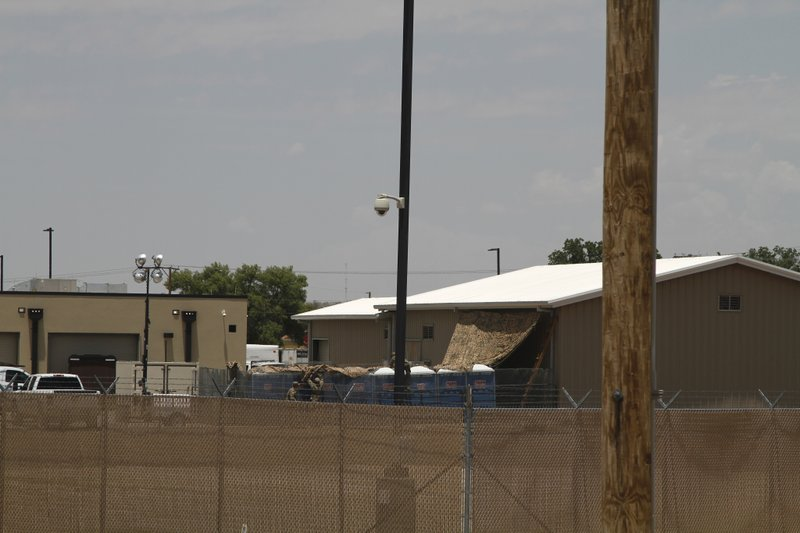 National Guard soldiers adjust a shade tarp over portable toilets adjacent to a building used for the detention of unaccompanied children in Border Patrol custody in Clint, Texas, Wednesday, June 26, 2019. Migrant children being housed at the Border Patrol facility near El Paso appeared mostly clean and were being watched by hallway monitors on Wednesday, less than a week since they reported living there in squalid conditions with inadequate food, water and sanitation. (AP Photo/Cedar Attanasio)