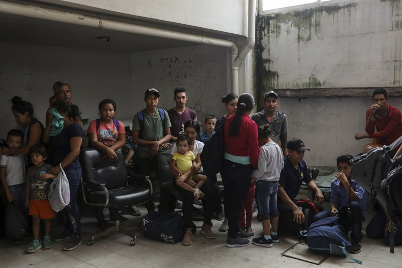 Migrants stand together as they're detained at the Azteca Hotel during a raid by Mexican immigration agents in Veracruz, Mexico, Thursday, June 27, 2019. Under increasing U.S. pressure to reduce the flow of hundreds of thousands of Central Americans through Mexican territory, Mexico's government has stepped up enforcement. (AP Photo/Felix Marquez)