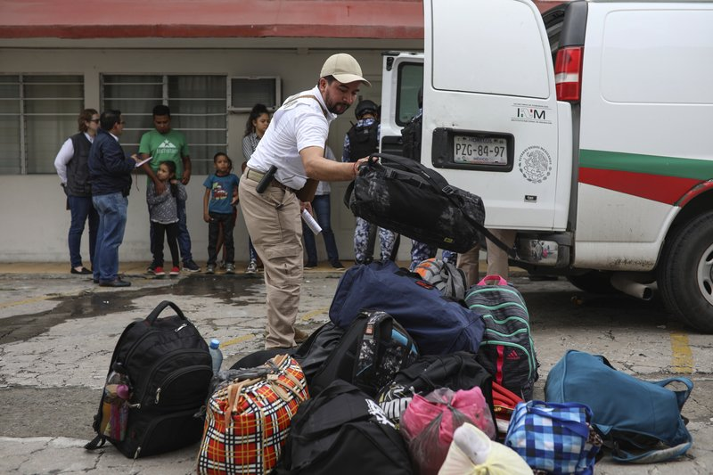 A Mexican immigration agent organizes the luggage of detained Central American migrants during a raid on the Latino hotel in Veracruz, Mexico, Thursday, June 27, 2019. Under increasing U.S. pressure to reduce the flow of hundreds of thousands of Central Americans through Mexican territory, Mexico's government has stepped up enforcement. (AP Photo/Felix Marquez)