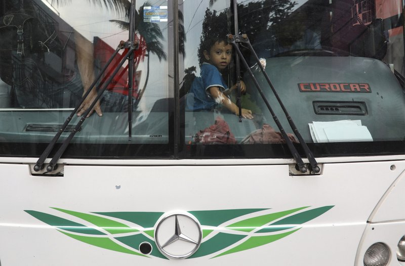 A young Central American migrant peers from the bus where he and other migrants are placed by  Mexican immigration agents during a raid at the Azteca Hotel in Veracruz, Mexico, Thursday, June 27, 2019. Under increasing U.S. pressure to reduce the flow of hundreds of thousands of Central Americans through Mexican territory, Mexico's government has stepped up enforcement. (AP Photo/Felix Marquez)