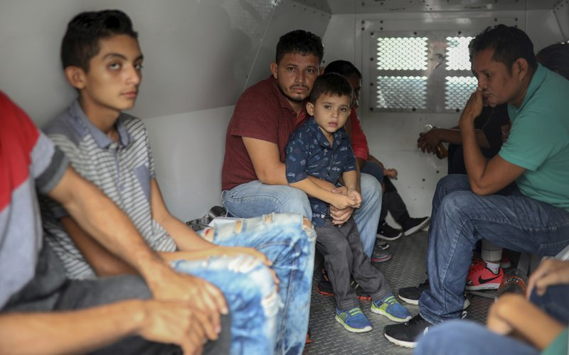 Central American migrants sit inside an immigration van during a raid on the Latino hotel by Mexican immigration agents in Veracruz, Mexico, Thursday, June 27, 2019. Under increasing U.S. pressure to reduce the flow of hundreds of thousands of Central Americans through Mexican territory, Mexico's government has stepped up enforcement. (AP Photo/Felix Marquez)