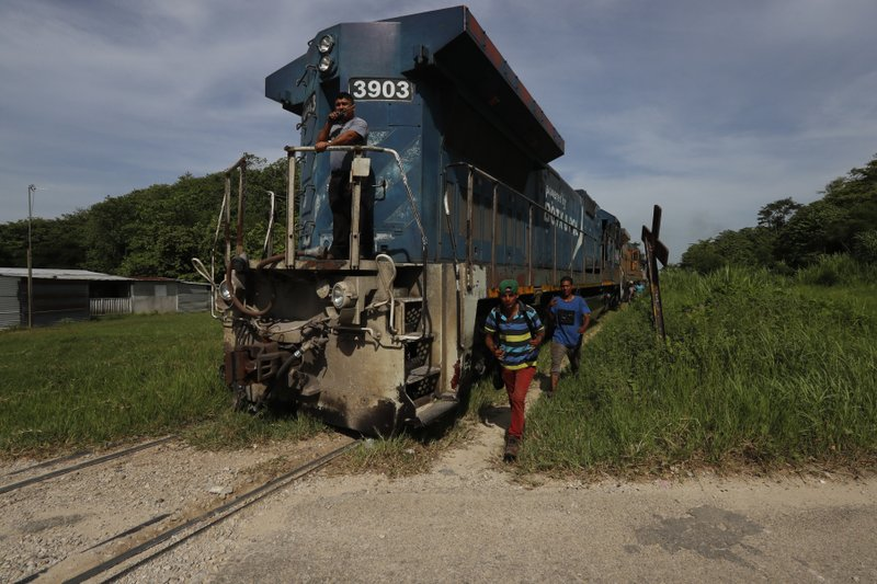 In this June 25, 2019 photo, migrants walk alongside a freight train headed north near Salto del Agua, Mexico. The government's renewed crackdown on migration, spurred by threats of tariffs by U.S. President Donald Trump, has pushed many back to risking a ride on a rattling train to advance though a remote stretch of southern Mexico with hopes of getting off and making their way by other means. (AP Photo/Marco Ugarte)