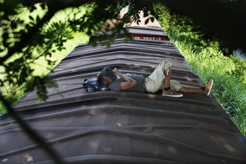 A Honduran migrant rides a freight train on his way north, in Salto del Agua, Mexico, Tuesday, June 25, 2019. Mexico has deployed 6,500 National Guard members in the southern part of the country, plus another 15,000 soldiers along its northern border in a bid to reduce the number of migrants traveling through its territory to reach the U.S. (AP Photo/Marco Ugarte)
