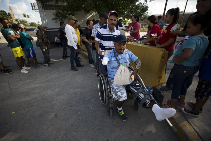 Jaime Lopez, 36, a Mexican citizen who says he fell from the freight train known by the migrants who ride it as La Bestia (Spanish for The Beast) three years ago and now plans to remain living in Mexico, collects food donated by a church group, at the Puerta Mexico international bridge, in Matamoros, Tamaulipas state, Mexico, Thursday, June 27, 2019. Hundreds of migrants from Central America, South America, the Caribbean and Africa have been waiting for their number to be called at the bridge in downtown Matamoros, to have the opportunity to request asylum in the U.S. (AP Photo/Rebecca Blackwell)