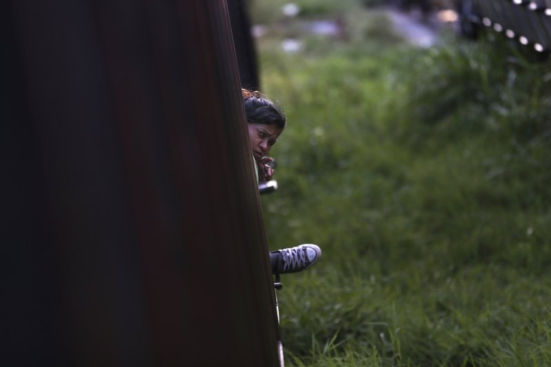 In this June 24, 2019 photo, a migrant looks out from the car of a freight train in Salto del Agua, Mexico. The Mexican crackdown on migrants prompted by pressure from the Trump administration has pushed Central American migrants to seek new ways to try to reach the U.S. border. (AP Photo/Marco Ugarte)