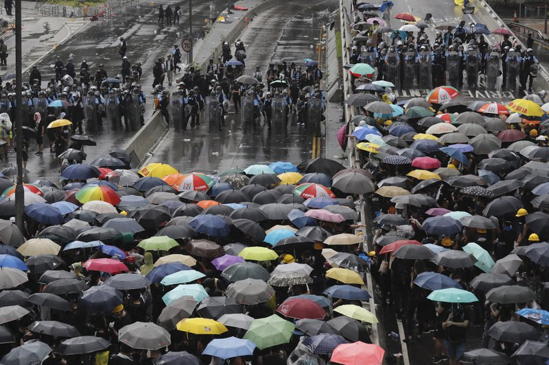 Protesters holding umbrellas face off police officers in anti-riot gear in Hong Kong on Monday, July 1, 2019. Protesters in Hong Kong pushed barriers and dumpsters into the streets early Monday morning in an apparent bid to block access to a symbolically important ceremony marking the anniversary of the return of the former British colony to China. (AP Photo/Kin Cheung)