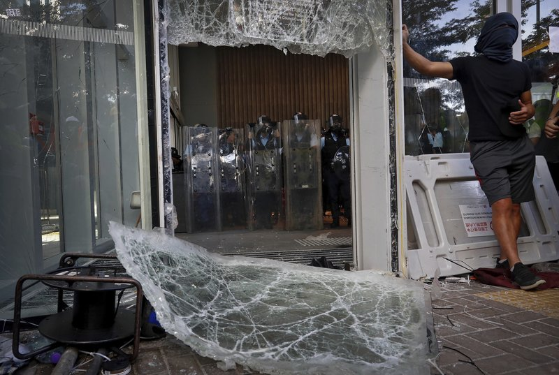 Police officers with shields stand guard behind the damaged glass of the Legislative Council after protesters try to break into in Hong Kong on Monday, July 1, 2019. Combative protesters tried to break into the Hong Kong legislature Monday as a crowd of thousands prepared to start a march in that direction on the 22nd anniversary of the former British colony's return to China. (AP Photo/Vincent Yu)