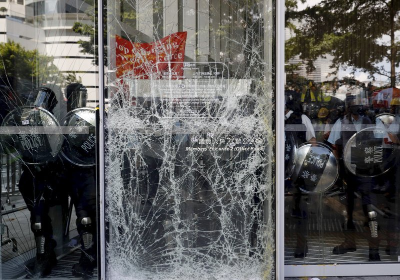Police officers stand guard behind the cracked glass wall of the Legislative Council after protesters try to break into in Hong Kong on Monday, July 1, 2019. Combative protesters tried to break into the Hong Kong legislature Monday as a crowd of thousands prepared to start a march in that direction on the 22nd anniversary of the former British colony's return to China. (AP Photo/Vincent Yu)