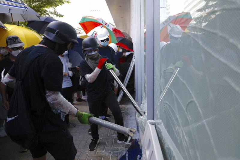 Protesters try to break the glass walls of the Legislative Council in Hong Kong on Monday, July 1, 2019. Combative protesters tried to break into the Hong Kong legislature Monday as a crowd of thousands prepared to start a march in that direction on the 22nd anniversary of the former British colony's return to China. (AP Photo/Vincent Yu)