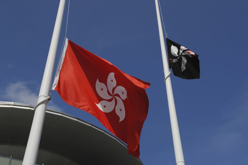A black Hong Kong flag flies as protesters replaced with the Chinese flag that is normally set up next to a Hong Kong flag, left, in Hong Kong on Monday, July 1, 2019. The Hong Kong government marked the 22nd anniversary of the former British colony's return to China on Monday, as police faced off with protesters outside the venue. (AP Photo/Kin Cheung)