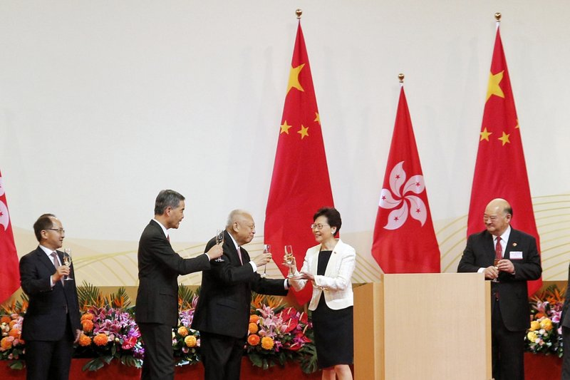 Hong Kong Chief Executive Carrie Lam, second right, toasts with former Chief Executives Tung Chee-hwa, third from left, and Leung Chun-ying, second from left, during a ceremony to mark the anniversary of the handover of Hong Kong to China, in Hong Kong Monday, July 1, 2019. The Hong Kong government marked the 22nd anniversary of the former British colony's return to China on Monday, as police faced off with protesters outside the venue. (Jacky Cheung/HK01 via AP)