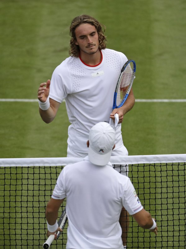 Italy's Thomas Fabbiano, back to camera, greets Stefanos Tsitsipas of Greece at the net after winning the Men's singles match during day one of the Wimbledon Tennis Championships in London, Monday, July 1, 2019. (AP Photo/Ben Curtis)