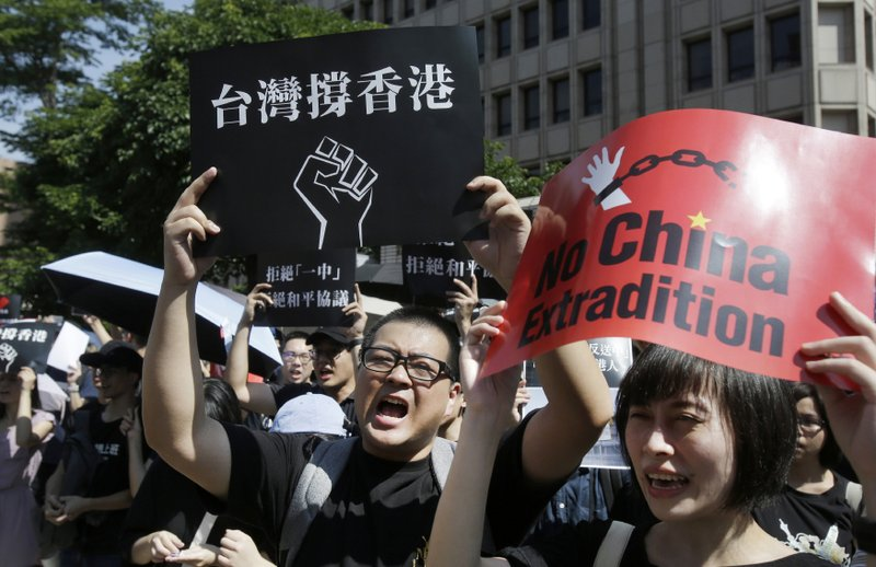 FILE - In this June 16, 2019, file photo, Hong Kong students and Taiwan supporters hold up cards which read