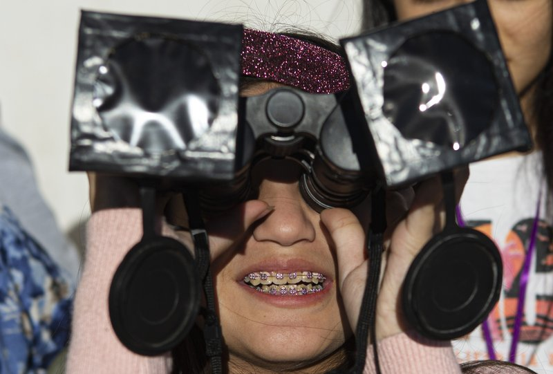 A girl tests special binoculars to view tomorrow's total solar eclipse near Central Park in La Higuera, Chile, Monday, July 1, 2019. Tourists and scientists will gather in northern Chile, one of the best places in the world to watch the next the eclipse that will plunge parts of South America into darkness. (AP Photo/Esteban Felix)