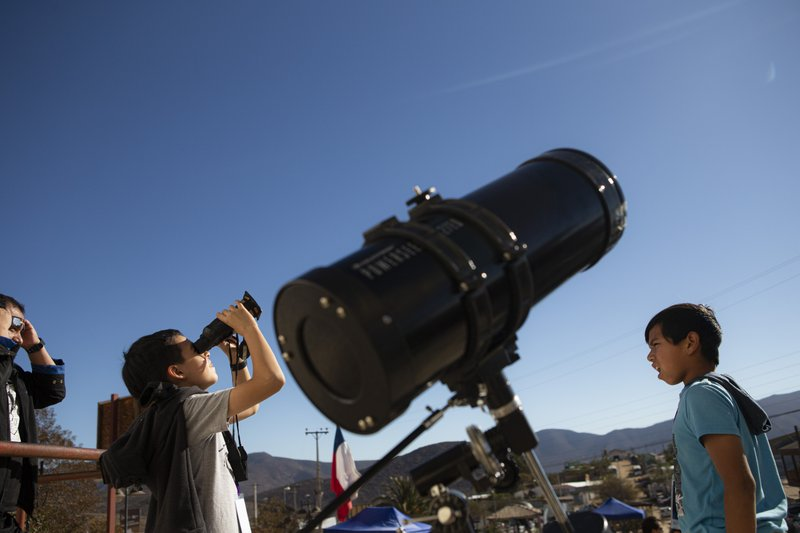 Children test out special binoculars to view tomorrow's total solar eclipse near Central Park in La Higuera, Chile, Monday, July 1, 2019. Tourists and scientists will gather in northern Chile, one of the best places in the world to watch the next the eclipse that will plunge parts of South America into darkness. (AP Photo/Esteban Felix)