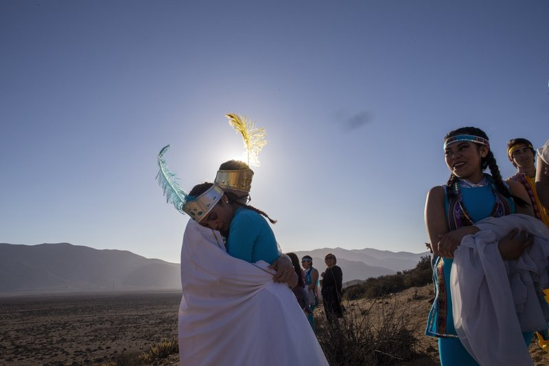 Girls dressed as Princess Sun and Princess Moon arrive to take part in a photo session before tomorrow's total solar eclipse in La Higuera, Chile, Monday, July 1, 2019. Tourists and scientists will gather in northern Chile, one of the best places in the world to watch the next the eclipse that will plunge parts of South America into darkness. (AP Photo/Esteban Felix)