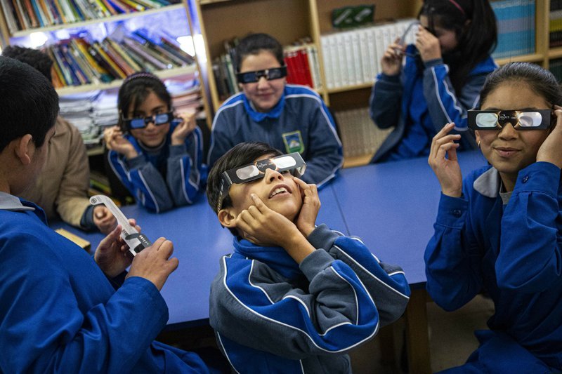 Children try on their special glasses to view tomorrow's total solar eclipse at Pedro Pablo Munoz school in La Higuera, Chile, Monday, July 1, 2019. Tourists and scientists will gather in northern Chile, one of the best places in the world to watch the next the eclipse that will plunge parts of South America into darkness. (AP Photo/Esteban Felix)