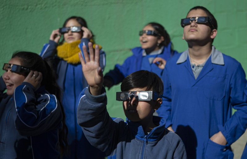 Children test on their special glasses for tomorrow's total solar eclipse at Pedro Pablo Munoz school in La Higuera, Chile, Monday, July 1, 2019. Tourists and scientists will gather in northern Chile, one of the best places in the world to watch the next the eclipse that will plunge parts of South America into darkness. (AP Photo/Esteban Felix)
