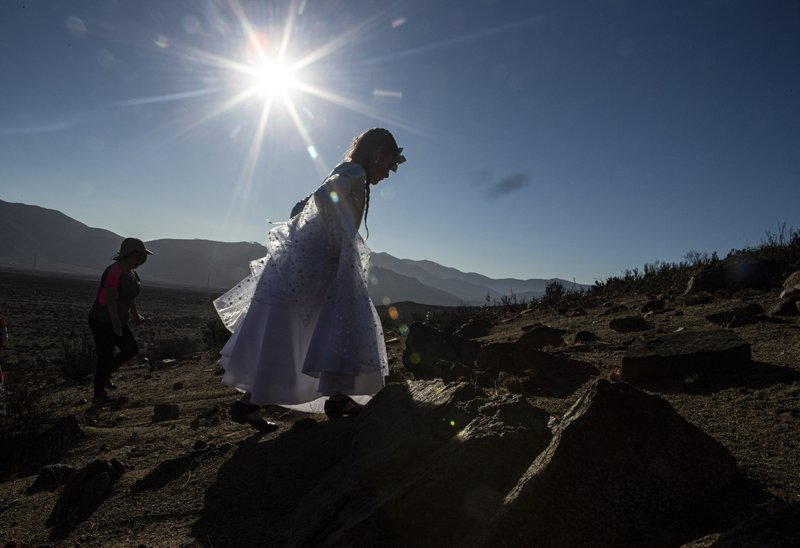 A girls dressed as a Daiguitas Indigenous person arrives to take part in a photo session before tomorrow's total solar eclipse in La Higuera, Chile, Monday, July 1, 2019. Tourists and scientists will gather in northern Chile, one of the best places in the world to watch the next the eclipse that will plunge parts of South America into darkness. (AP Photo/Esteban Felix)
