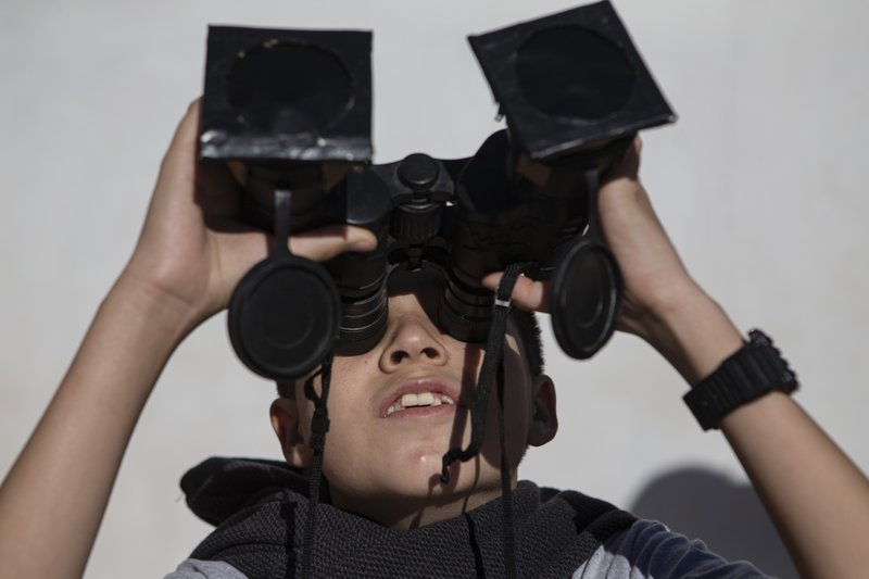 A youth tests special binoculars to view tomorrow's total solar eclipse near Central Park in La Higuera, Chile, Monday, July 1, 2019. Tourists and scientists will gather in northern Chile, one of the best places in the world to watch the next the eclipse that will plunge parts of South America into darkness. (AP Photo/Esteban Felix)