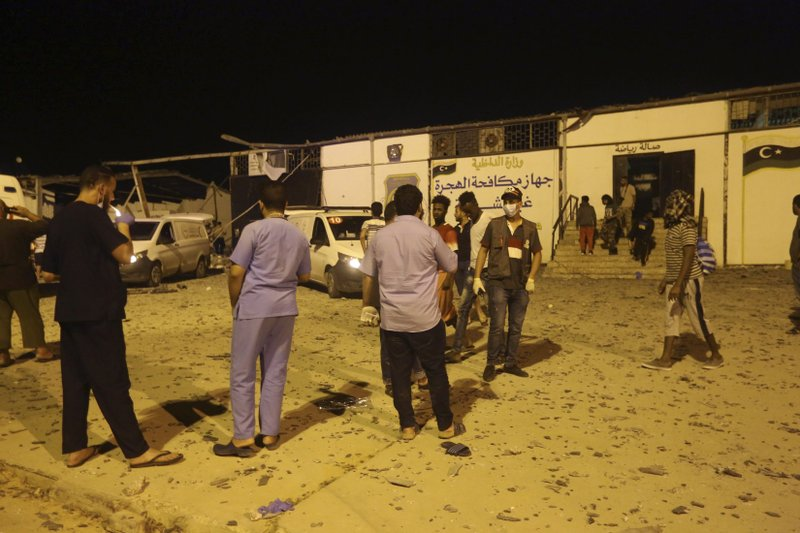 Workers gather at a detention center after an airstrike in Tajoura, east of Tripoli Wednesday, July 3, 2019. An airstrike hit the detention center for migrants early Wednesday in the Libyan capital. (AP Photo/Hazem Ahmed)