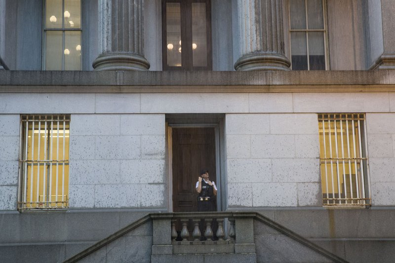 A Uniformed Division Secret Service officer looks up at the rain as he takes shelter in a doorway of the Treasury Building, Monday, July 8, 2019, in Washington. (AP Photo/Alex Brandon)