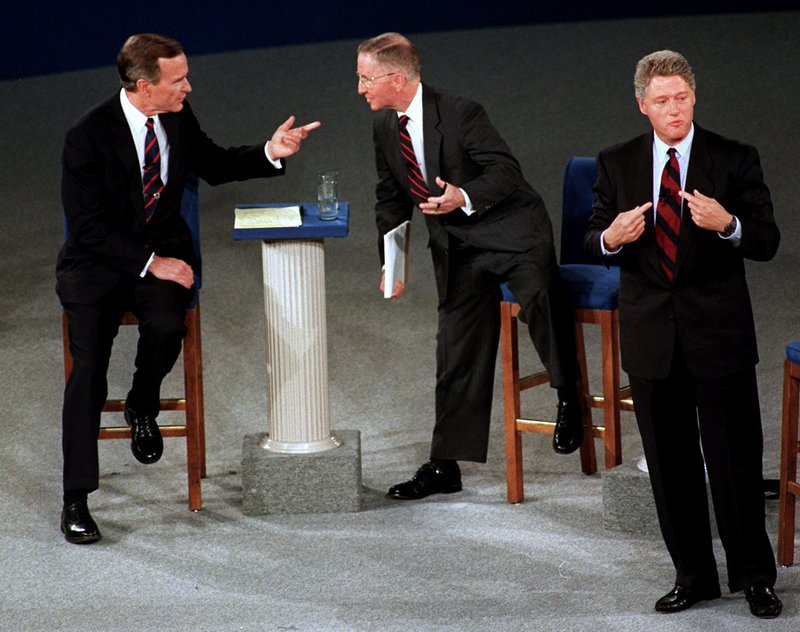 FILE - In this Oct. 15, 1992, file photo, President George H.W. Bush, left, talks with independent candidate Ross Perot as Democratic candidate Bill Clinton stands aside at the end of their second presidential debate in Richmond, Va. Perot, the Texas billionaire who twice ran for president, has died, a family spokesperson said Tuesday, July 9, 2019. He was 89. (AP Photo/Marcy Nighswander, File)