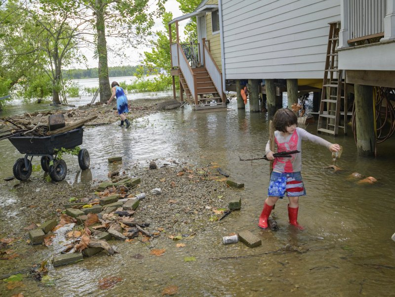 Delilah Campbell, 4, right, and her sister, Tallulah Campbell, 8, clear driftwood and other debris in preparation of Tropical Storm Barry near New Orleans, La., Thursday, July 11, 2019. The area is normally a driveway at her family's home that is one of the few on land called batture on the outside of the Mississippi River levee at the border of Orleans and Jefferson Parishes. (AP Photo/Matthew Hinton)