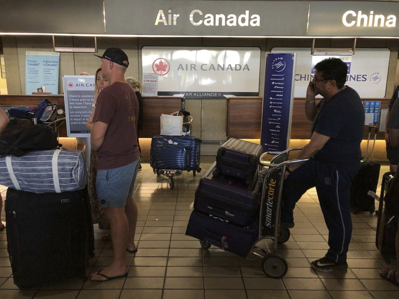 Passengers from an Australia-bound Air Canada flight diverted to Honolulu Thursday, July 11, 2019, after about 35 people were injured during turbulence, stand in line at the Air Canada counter at Daniel K. Inouye International Airport to rebook flights. Air Canada said the flight from Vancouver to Sydney encountered