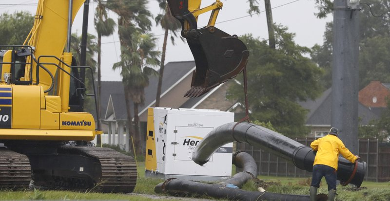 A worker maneuvers a section of pipe to the ground as a crew raced to install drainage pumps in west Morgan City, La., Saturday morning July 13, 2019, as the winds and rain of Hurricane Barry approach. (AP Photo/Rogelio V. Solis)