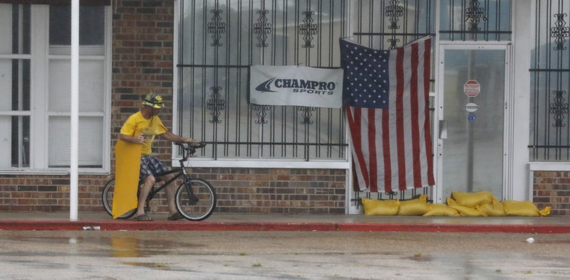 Gordon Helman carries a business poster he picked up from the road as he rides his bike through stiff winds and stinging rain in Morgan City, La., Saturday morning, July 13, 2019.  Helman said he was bored at home and wanted to