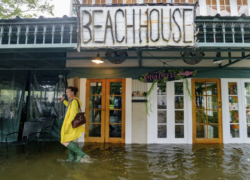 Aimee Cutter,  the owner of Beach House restaurant, walks through water surge from Lake Pontchartrain on Lakeshore Drive in Mandeville, La., ahead of Tropical Storm Barry, Saturday, July 13, 2019.  Barry is expected to reach hurricane strength by the time its center reaches the Louisiana coast, expected before noon local time. The storm is expected to weaken after it moves inland.  (AP Photo/Matthew Hinton)