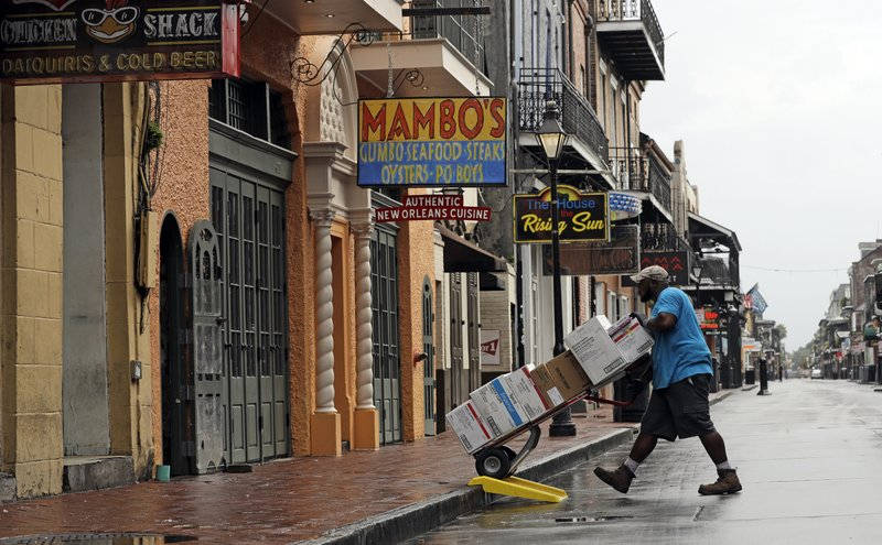 Fred Foster makes a delivery on Bourbon Street in the French Quarter Saturday, July 13, 2019, in New Orleans, as Tropical Storm Barry nears landfall. (AP Photo/David J. Phillip)