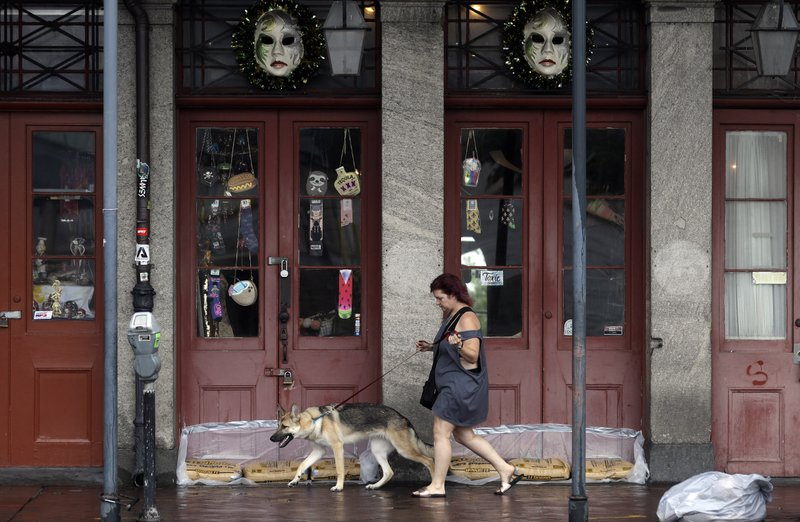 Alonda Da Costa walks her dog, Ohanna, in the French Quarter Saturday, July 13, 2019, in New Orleans, as Tropical Storm Barry nears landfall. (AP Photo/David J. Phillip)